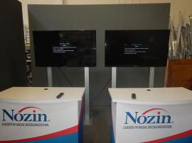 "RENTAL: (2) RE-1229 Large Monitor Kiosks with Black Laminated Shelves on Back Side, (2) 55"" Monitors, (2) RE-1558 Gravitee Counters with Locking Doors and Interior Shelves, and Silicone Edge Fabric Graphics for Counters"